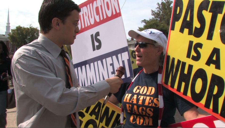 "Click photo to download. Caption: Jewish comedian Dave Sirus plays his ""reporter"" role to counter a demonstrator from the Westboro Baptist Church. Credit: Courtesy Dave Sirus."
