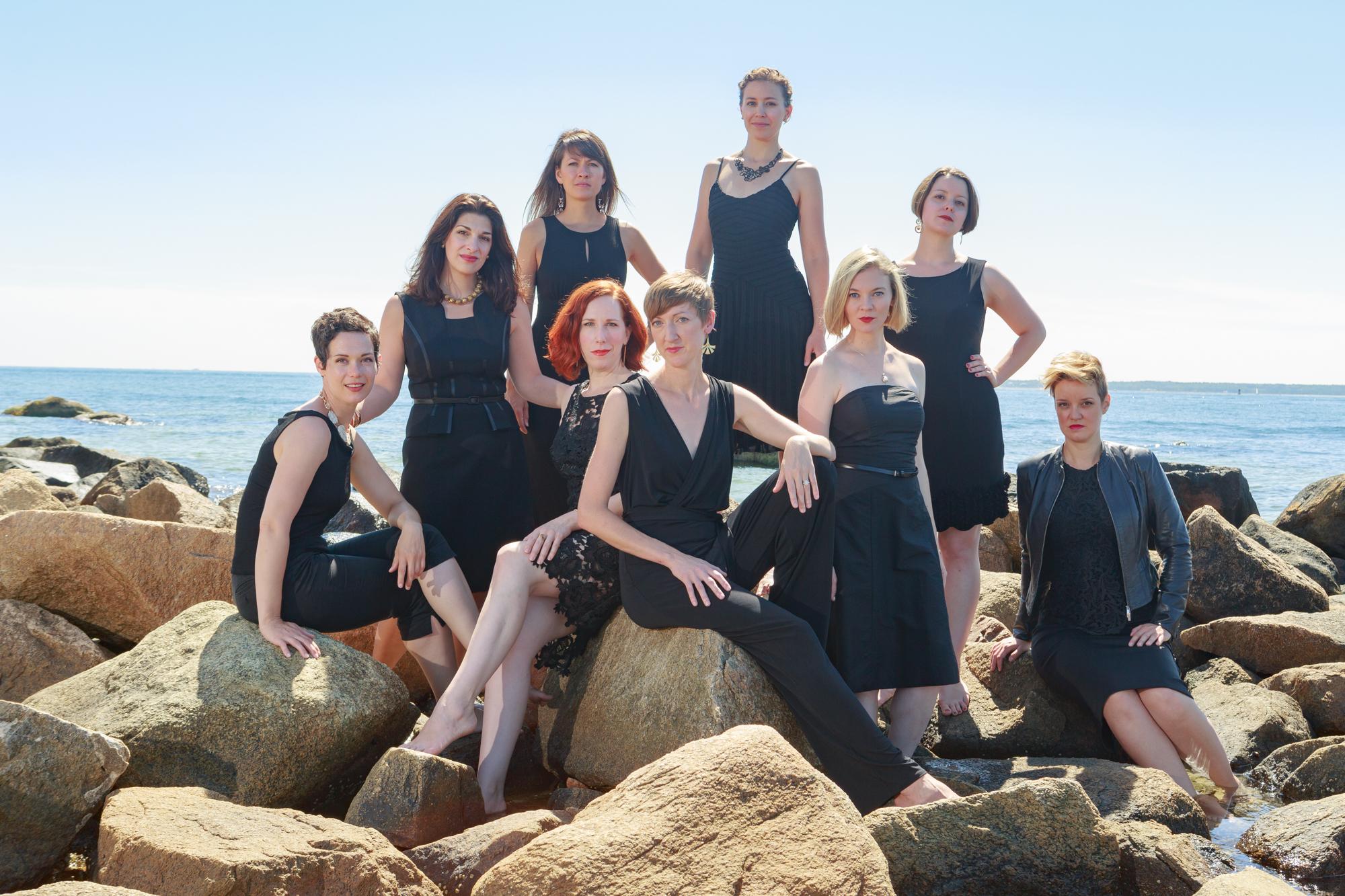 Lorelei Ensemble singers posed on rocks by sea
