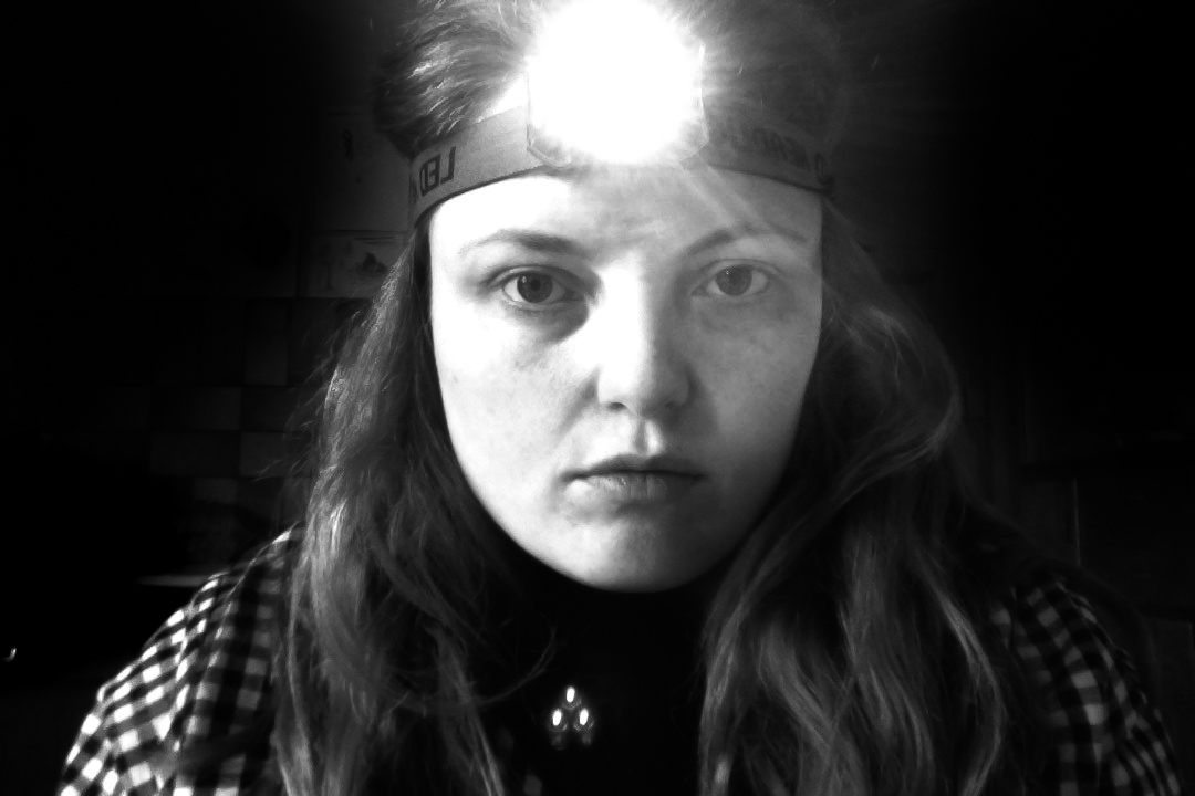 black and white photo of author wearing head lamp