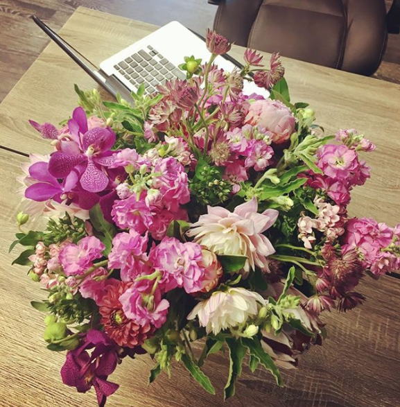 Pink flowers on desk with computer