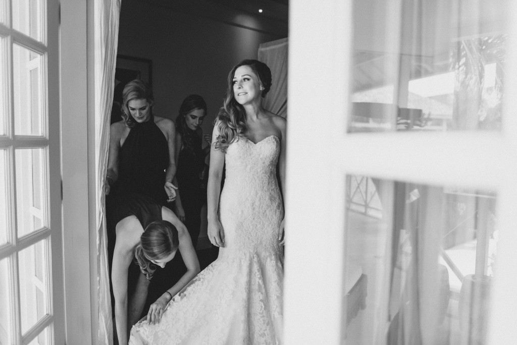 A bridesmaid helps her bride fix the dress