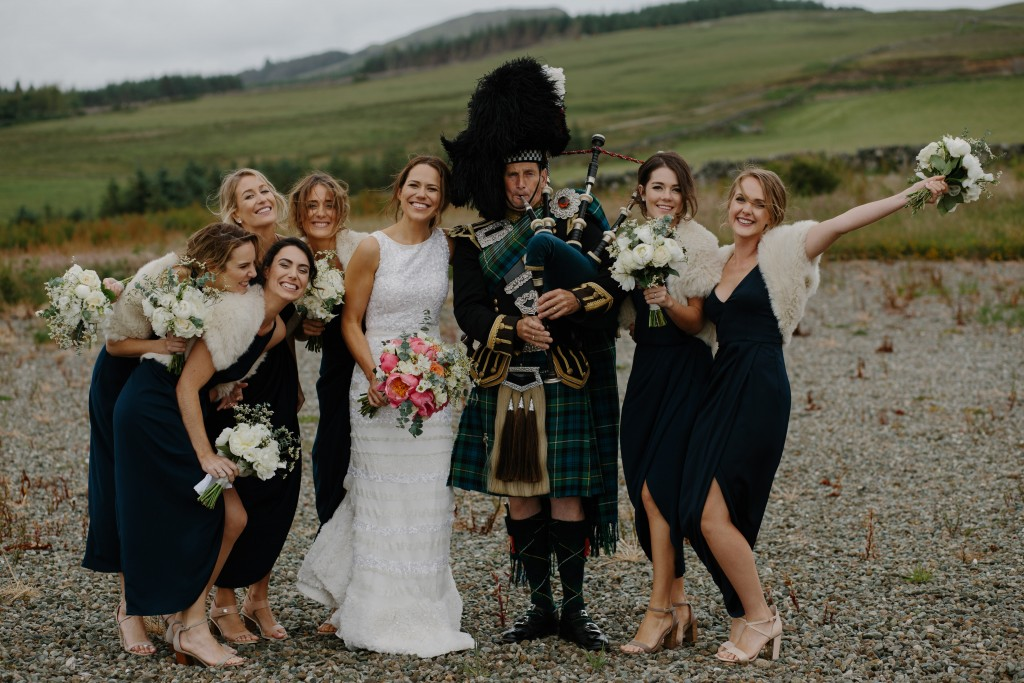 Bridesmaids and their bride with a Scottish bagpipe player
