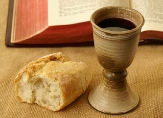 Bread and wine next to a bible