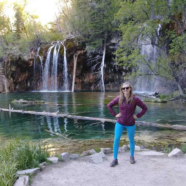 kayla posing in front of a beautiful waterfall