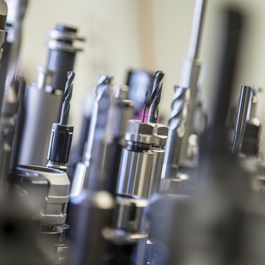 Assortment of CNC machine tools including end mills, spot drills and reamers for high precision cutting.