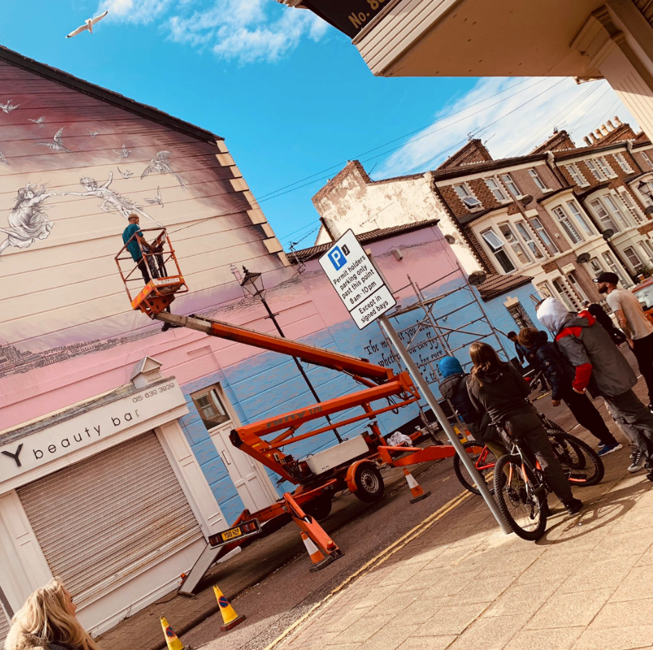 Man in cherry picker painting mural on the side of a building